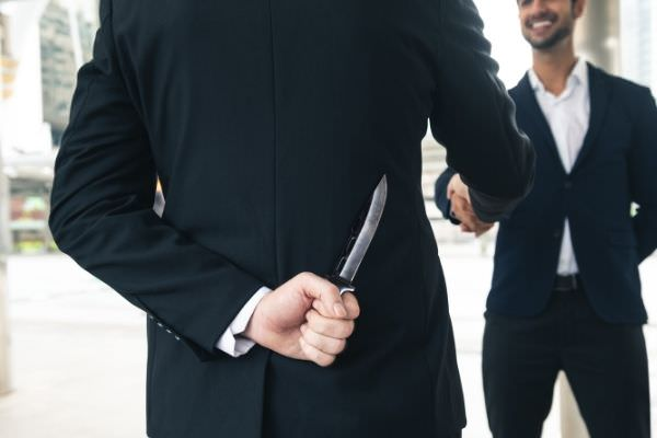 07 two business making handshake deal hiding knife on the back