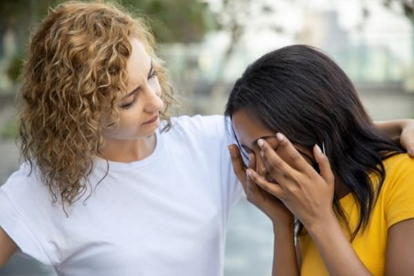 01 woman with curly hair white shirt good friend giving encouragement her